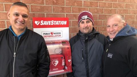 Trois hommes regardent la caméra à côté d'un défibrillateur à l'extérieur d'une maison.