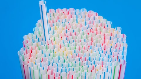 Une paille ressort d'une pile de pailles colorées.