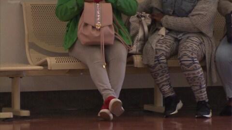 Des femmes assises sur un banc en Chambre de la jeunesse. On ne voit pas leur visage.