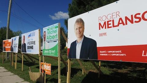 Des pancartes du Parti vert, du Parti progressiste-conservateur, du Parti libéral et du Nouveau Parti démocratique sont installées au même endroit.