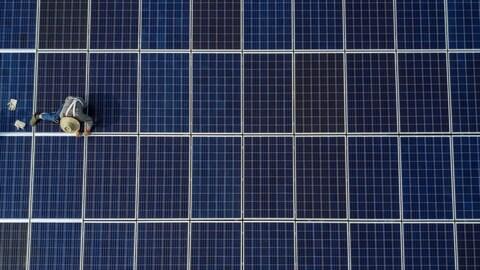 Un ouvrier chinois pose des panneaux solaires au sommet d'un immeuble.