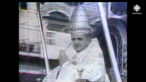 Le pape PaulVI, habillé avec son habit de cérémonie, est assis sur un trône.