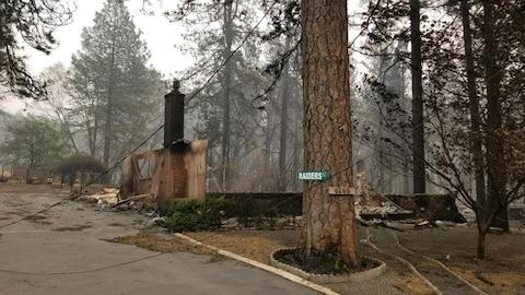 Une maison brûlée entourée d'arbres.