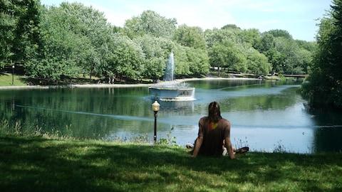 Un homme est assis sur l'herbe devant le bassin du parc La Fontaine à Montréal.