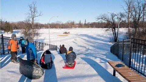 Des enfants glissent sur la neige en hiver.