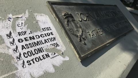Une affiche a été collée sur la statue de John A. Macdonald dans le parc Victoria à Regina. L'affiche mentionne les mots comme: « génocide», « assimilation », et « colonisation. »