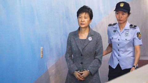 L'ancienne présidente sud-coréenne Park Geun-hye arrive en cour escortée par une policière, à Séoul, le 25 août 2017.