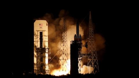 Une fusée dégage des colonnes de fumée et de feu lors du lancement de ses propulseurs en pleine nuit.