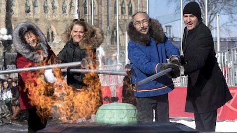 La commissaire du Nunavut Nellie Kusugak, la gouverneure générale Julie Payette, lepremier ministre du Nunavut Paul Quassa et le premier ministre canadien Justin Trudeau allument la flamme du Centenaire à Ottawa qui comporte désormais les symboles officiels du Nunavut