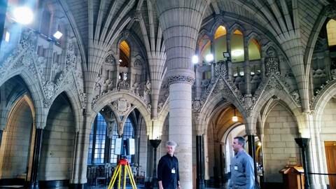 On voit deux hommes dans l'édifice du centre du parlement d'Ottawa, à côté d'eux se trouve un appareil de mesure sur trépied : autour d'eux, on voit les colonnes, les arches, les alcôves.