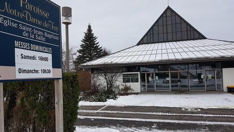 La paroisse de Notre-Dame-de-Foy vue de face, avec le panneau des horaires de messe au premier plan.