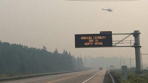 Un signal routier indiquant une visibilité réduite en raison de la fumée