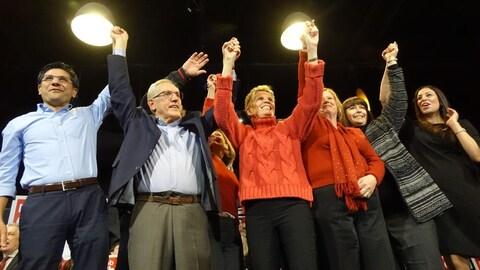 Des hommes et des femmes politiques lèvent les bras en signe de solidarité.