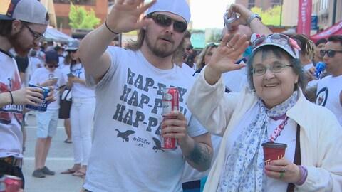Un jeune homme et une femme, plus âgée, saluent la caméra. Ils portent du blanc, pour célébrer les Jets de Winnipeg, et sont entourés d'autres partisans lors d'un rassemblement extérieur.