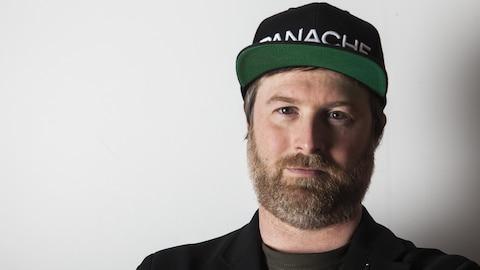Une photo montrant Patrice Désilets. Il porte une casquette noire sur laquelle est brodé le mot Panache en blanc.