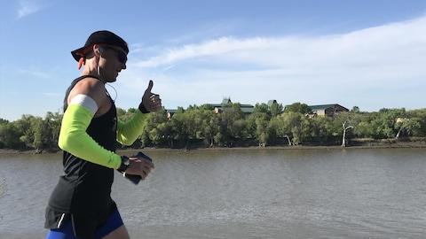 Un homme en bonne forme physique court le long d'une rivière.