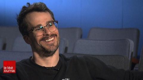 Patrick Hivon sourit assis dans un fauteuil.