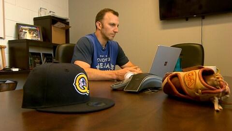 Patrick Scalabrini navigue sur Internet à l'aide de son ordinateur portable dans son bureau du stade Canac. Une casquette des Capitales et un gant de baseball sont déposés sur son bureau.