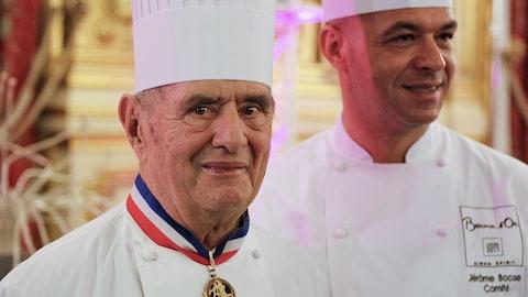 Paul Bocuse est coiffé d'une toque blanche. À son cou,  il porte sa médaille de Meilleur ouvrier de France.