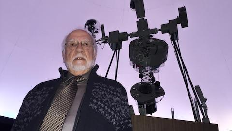Paul-Émile Legault sous le dôme du planétarium, près d'un grand projecteur.