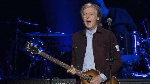 Paul McCartney joue de la guitare basse sur une scène devant une foule.