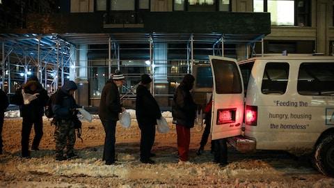 Des gens font la queue dans la rue pour recevoir de l'aide.