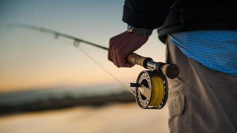Un homme tient une canne à pêche de sa main gauche.