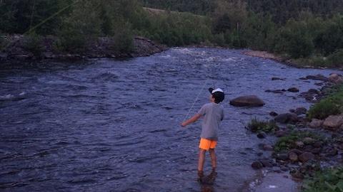 Un jeune garçon pêche à la mouche dans une rivière calme entourée de forêt.