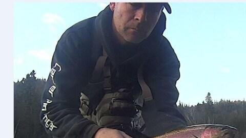 Un pêcheur inconnu tient une truite.