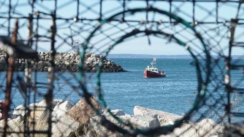 Un petit bateau de pêche sur lequel flotte un drapeau mi'kmaq est photographié à travers le trou dans les cordages d'un casier à homard.