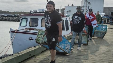 Quatre hommes marchent à la file sur une quai en traînant des casiers à homard.