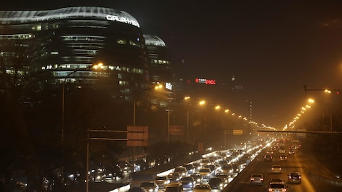 Autoroute très éclairée encerclant le centre de Pékin, en Chine, lors de l'heure de pointe du soir.
