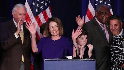 Cinq personnes, dont un enfant, applaudissent et saluent de la main.