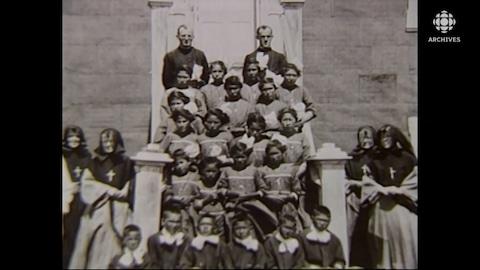 Photo de groupe d'enfants autochtones, avec des religieux et des sœurs autour d'eux.
