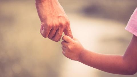 Une père et sa fille se prenant la main.