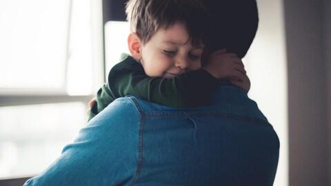 Un père prend son fils dans ses bras