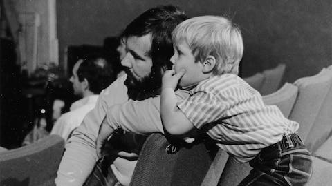 Un père et son fils tournés vers la scène d'un amphithéâtre, le fils appuyé sur l'épaule du père.