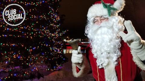 Un père Noël brandit une cloche devant un énorme sapin de Noël illuminé.