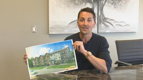 Le promoteur tient un plan de ce à quoi ressemblerait l'immeuble résidentiel.