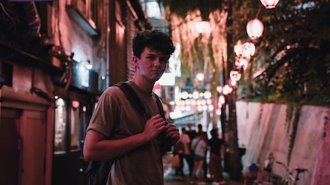 L'artiste Petit Biscuit pose sur une rue éclairée de lanternes.