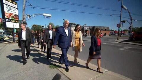 Philippe Couillard marche avec un groupe de personnes sur un boulevard de la circonscription de Sainte-Rose, où on peut apercevoir l'enseigne d'un restaurant.