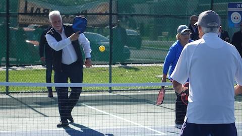 M. Couillard frappe une balle avec sa raquette.