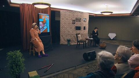 Deux comédiennes discutent au téléphone lors d'une scène. Des spectatrices les observent attentivement.