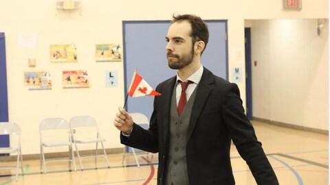 Un homme porte un costume sombre et tient dans sa main droite un drapeau canadien.