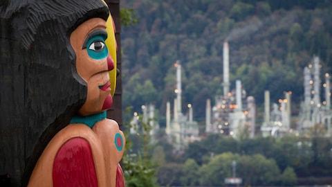 Un totem de profil avec en arrière-plan de la forêt et une usine de pétrole.