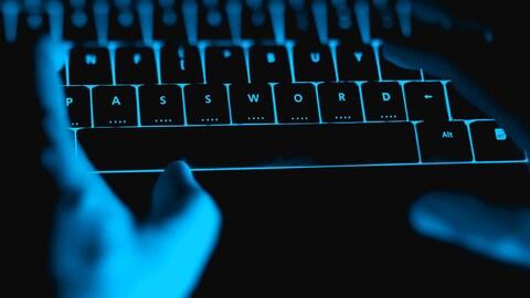 Des mains tapent sur un clavier rétroéclairé.