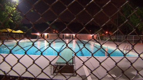 Une piscine est calme et fermée après ses heures habituelles d'ouverture.