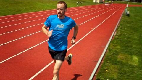 Un athlète en short et en t-shirt s'entraîne sur une piste de course à pied située à l'extérieur.