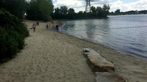 Un sauveteur marche sur le sable, près de l'eau, sur l'île Charron.