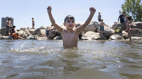 Un jeune garçon, dans l'eau jusqu'à la taille, avec les bras en l'air.